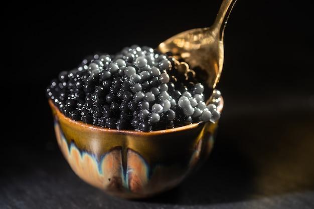 Pot met zwarte kaviaar en lepel met zwarte kaviaar