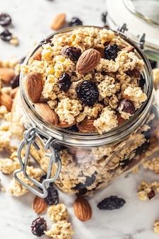 Pot muesli met noten, amandelen, druiven en gedroogde vruchten - close-up.