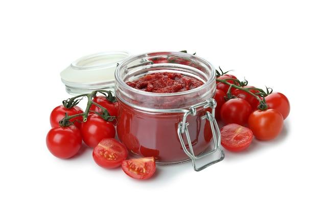 Pot tomatenpuree en tomaten geïsoleerd op een witte achtergrond