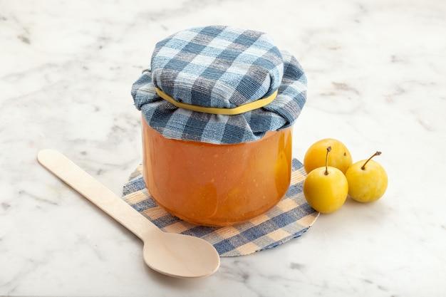 Pot van pruimjam en fruit op wit marmer