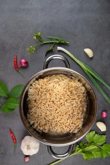 Pot van rauwe instant noodle met ingrediënten van soep op zwarte muur.