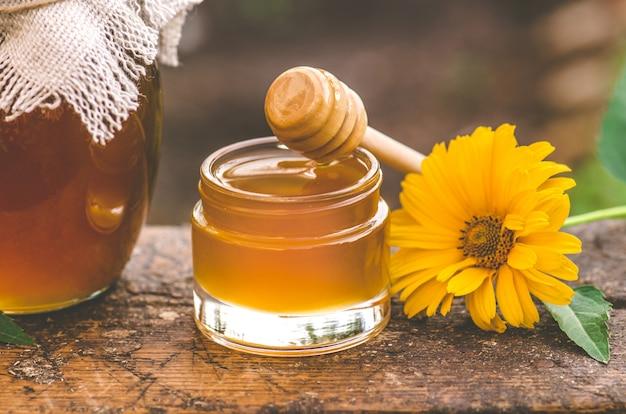 Pot verse honing, houten honingdipper en honingraten op gebied van wilde bloemen. honing en houten drizzler op tafel in de buurt van veld van wilde bloemen