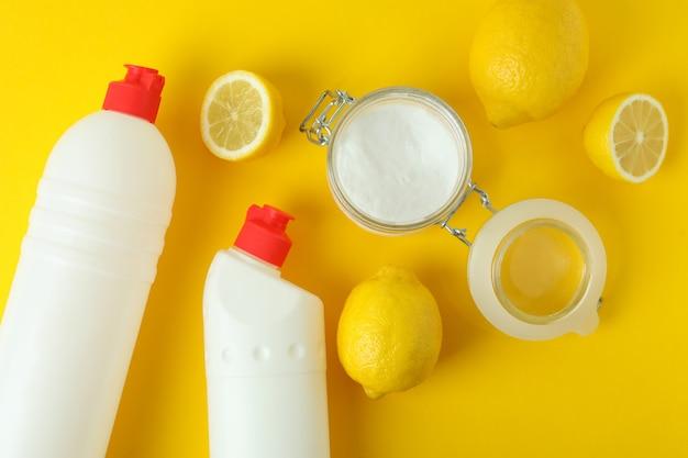 Pot zuur poeder, citroenen en wasmiddelen op gele geïsoleerde achtergrond