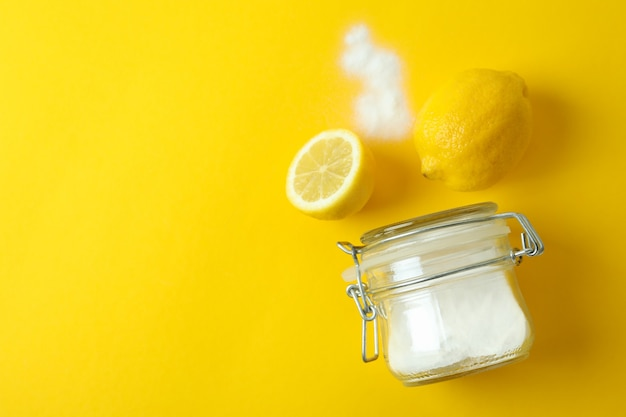 Pot zuur poeder en citroenen op gele geïsoleerde achtergrond