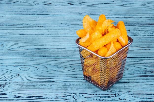 Potato chips en corn sticks in een ijzeren mand op houten tafel.