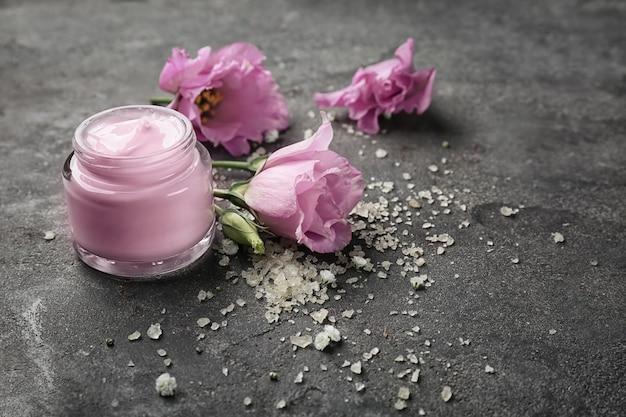 Potje lichaamscrème en bloemen op grijs beton