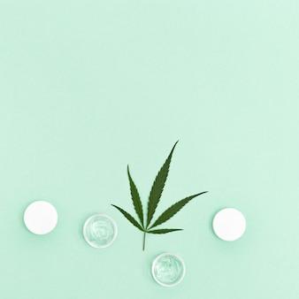 Potje met crème of gel voor gezicht en natuurlijk blad van cannabis