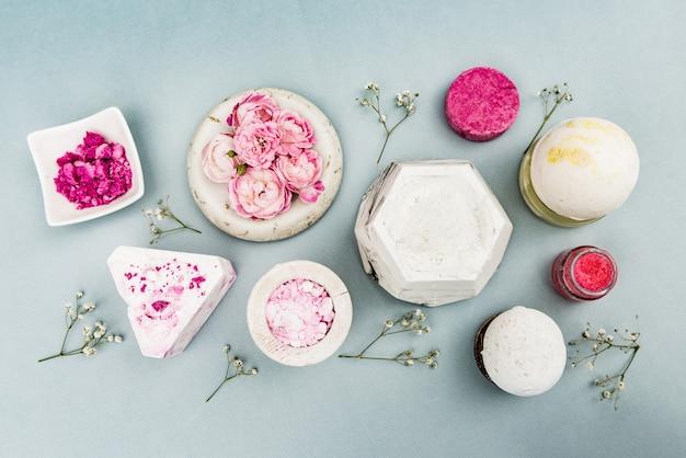 Potje met een zelfgemaakte hydraterende schoonheidscrème, rozenbloem, geïnfuseerd water of olie, kokosolie, rozenmengsel of gearomatiseerd water in een spuitfles, hydrolyt, was, roze klei, zeep
