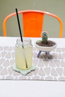 Potje met limonade en een cactus op tafel met een rode stoel