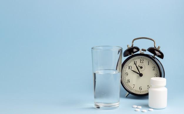 Potje pillen, water en een klok op een blauwe tafel. tijd om pillen te slikken. slapeloosheid. kopieer ruimte.