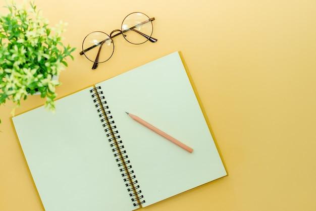 Potloden, bril en kladblok op een beige abstracte achtergrond