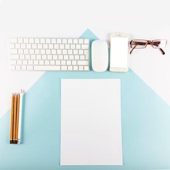 Potloden en papier in de buurt van gadgets en glazen