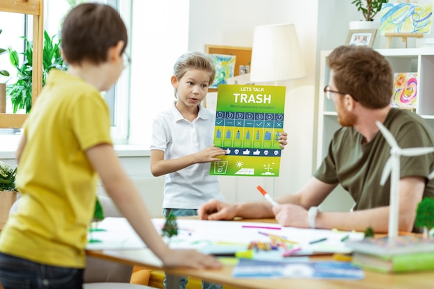 Potloden en stiften. vastberaden blonde kleine jongen met een educatieve poster over afvalrecycling en deze tijdens de lessen presenteert