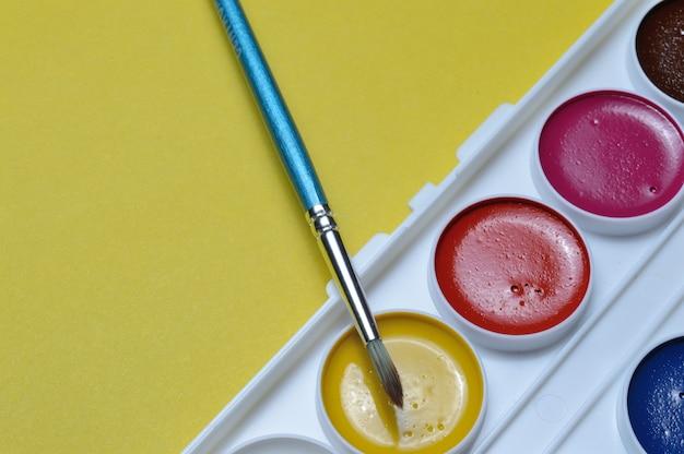 Potloden en verven in een palet op een gele achtergrond.