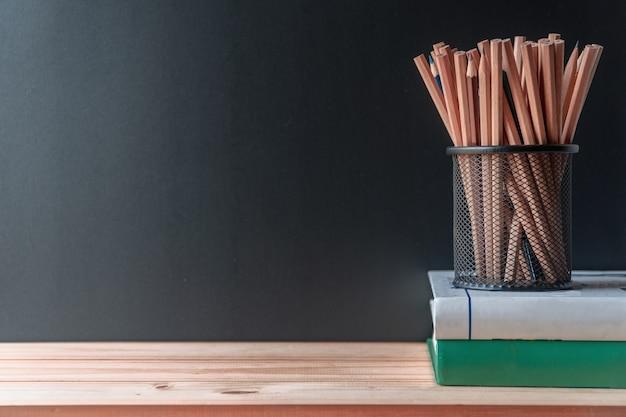 Potloden in de pot van de metaalhouder met boeken op houten lijst en bordachtergrond