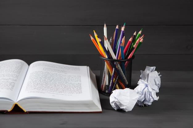 Potloden in een standaard, propjes papier een boek op tafel