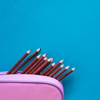 Potloden in geval op blauwe oppervlakte