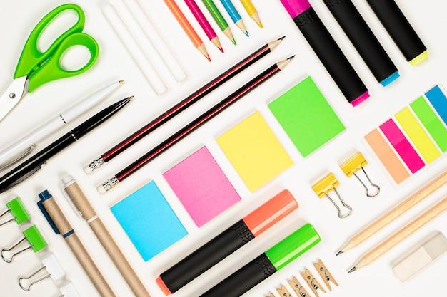 Potloden, pennen, stickers, scharen, paperclips, kleurpotloden, markeerstiften, clips en een gum worden met behulp van de knoltechniek op een lichte achtergrond neergelegd