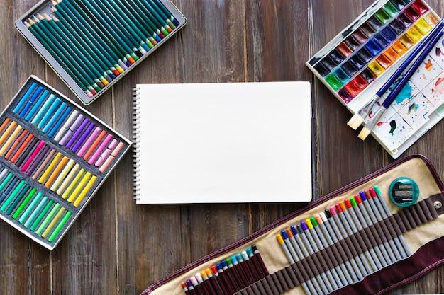 Potloden, penselen, aquarelverf, papier en pastelkrijt