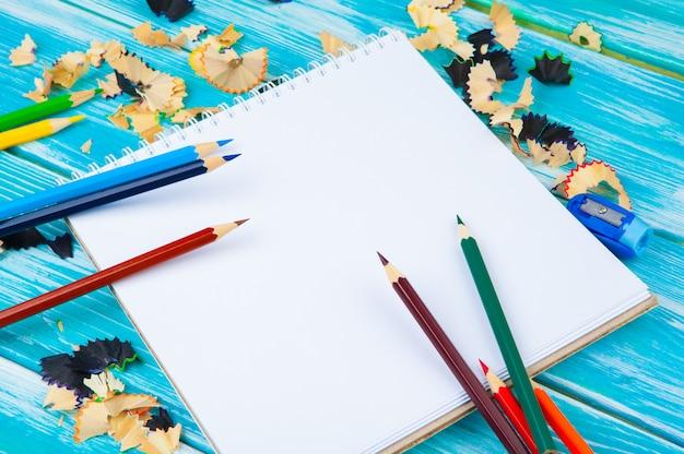 Potloden, potloodsneden en blanco papier op een bureaulijst