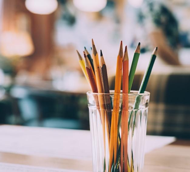 Potloden van meerdere kleuren in een glas