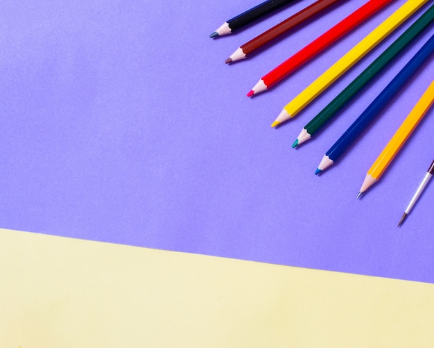 Potloden van regenboogkleuren op vellen geel lila papier. concept terug naar school, tekenen. minimalisme, plat leggen, ruimte kopiëren, bovenaanzicht