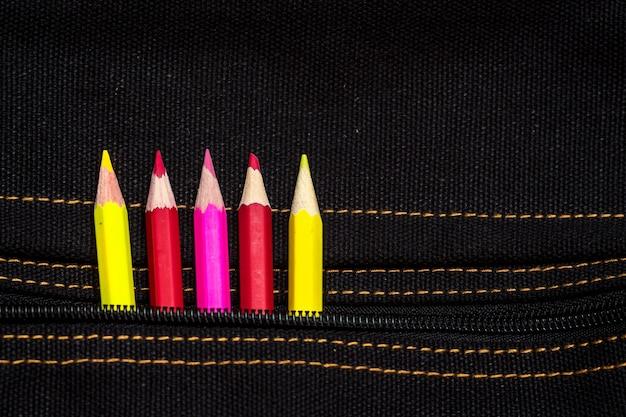 Potloden van rode, gele en roze kleur gluren uit de zak van de tas
