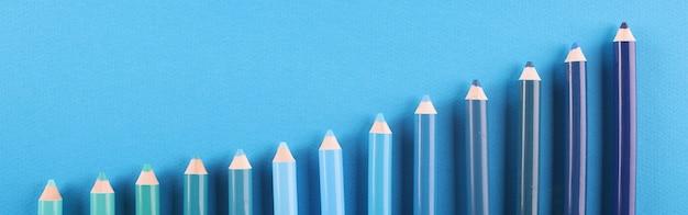 Potloden van verschillende tinten liggen op een blauwe achtergrond