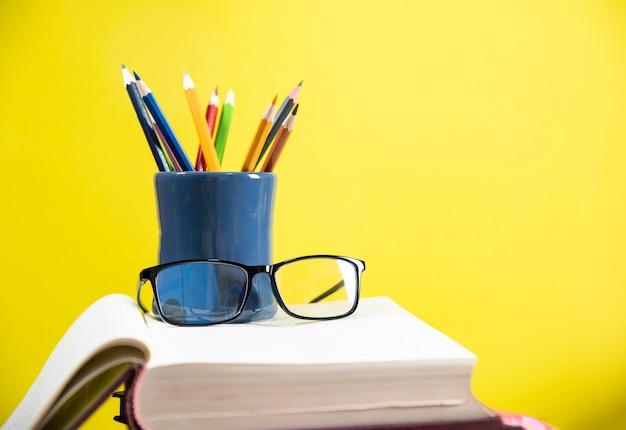 Potlodenkleur in een potloodgeval en glazen op een boek