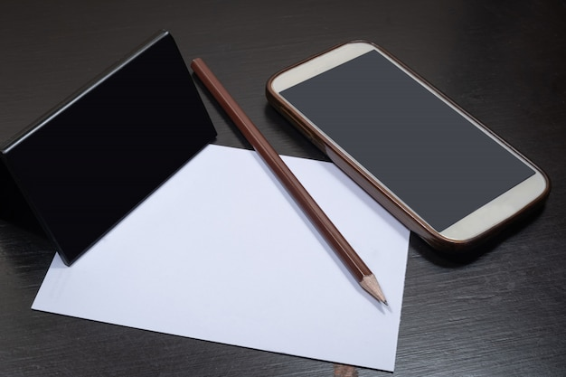 Potlood dat op witboek en smartphone wordt geplaatst