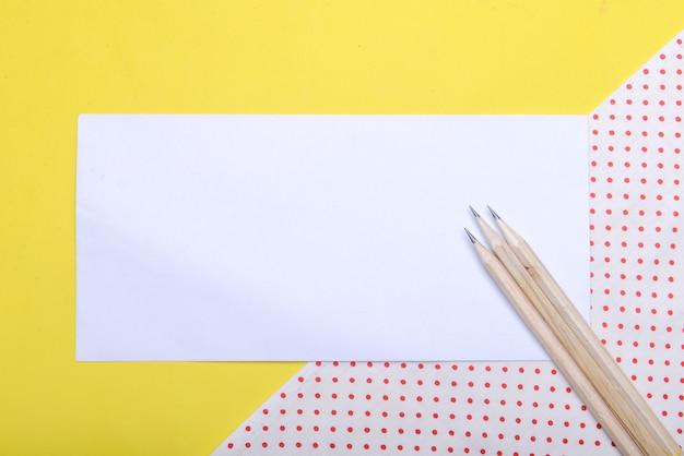 Potlood en leeg wit papier met een gekleurde achtergrond. leeg witboek voor exemplaarruimte Premium Foto