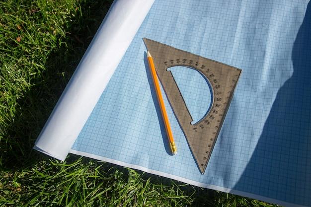 Potlood en liniaal op blauwdrukpapier liggend op groen gras