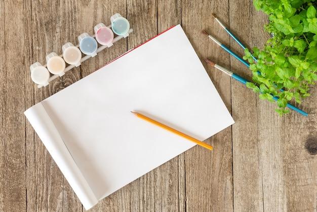 Potlood en schetsboek samen met verf en borstels