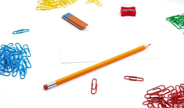 Potlood, gum, puntenslijper, paperclips liggen in verschillende hoeken van het blad op een witte achtergrond. held afbeelding en kopie ruimte.