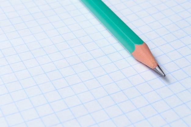 Potlood ligt op een vel notitieboekje. detailopname.