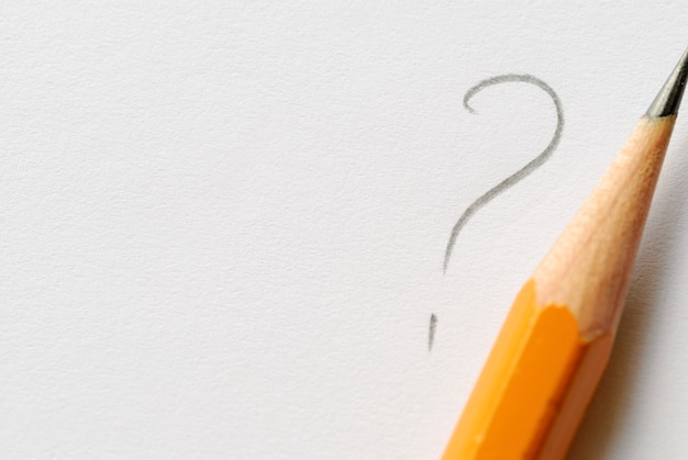 Potlood naast vraagteken op wit papier