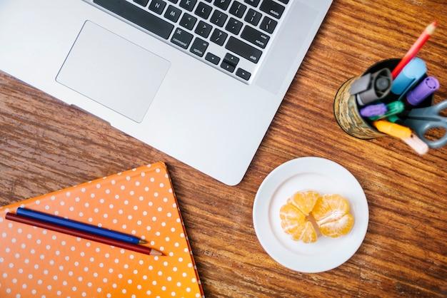 Potlood; notebook; laptop en oranje op houten bureau