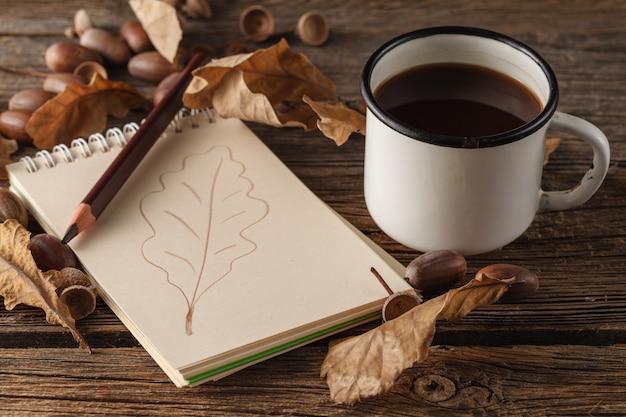 Potlood op de lege vintage papier, herfstbladeren op houten tafel. terug naar school concept: papier, potloden en kleurrijke bladeren.
