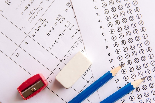 Potlood, puntenslijper en gum op antwoordbladen of gestandaardiseerd testformulier met antwoorden bubbl