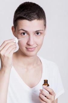 Potrait jonge vrouw die gezichtsproduct toepast