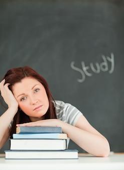 Potrait van een vermoeide jonge vrouw die studeert