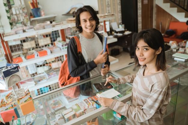 Potrait vrolijke vrouwelijke kassier die klanten bedient die briefpapier kopen