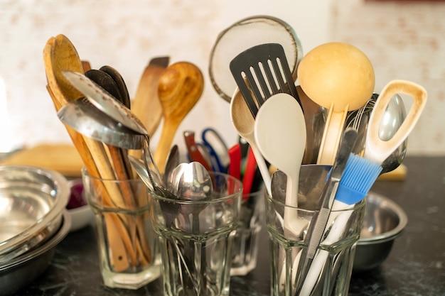 Potten gevuld met kookgerei zittend op een marmeren keukenbank.