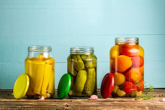 Potten met augurken van courgettes, komkommers, tomaten op een blauwe, houten achtergrond. voorraad voedsel