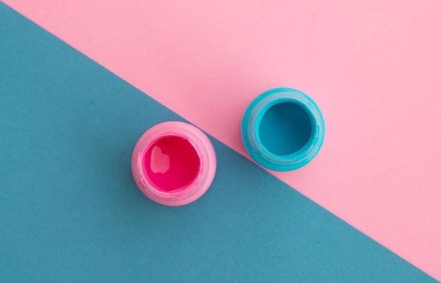 Potten met blauwe en roze verf op een diagonale achtergrond. bovenaanzicht.