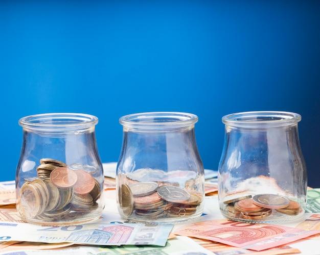 Potten met munten op bankbiljetten