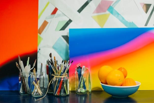 Potten met tekenbenodigdheden bij schilderijen en fruit