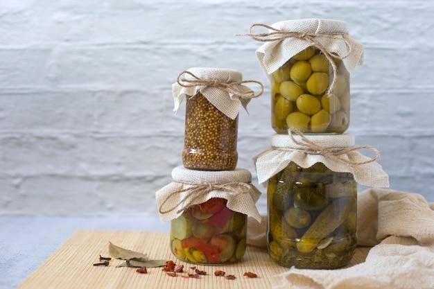 Potten van ingemaakte groenten op witte muurachtergrond. ingelegde komkommers, olijven, volkoren mosterd, salade. gefermenteerd voedsel