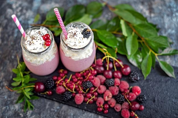 Potten van milkshake met veenbessen, aardbeien en bosbessen