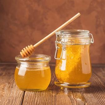 Potten van verse gouden honing en honinglepel op houten op tafel.